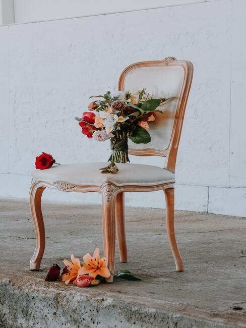 houten stoel met witte kussens en een vaas met bloemen
