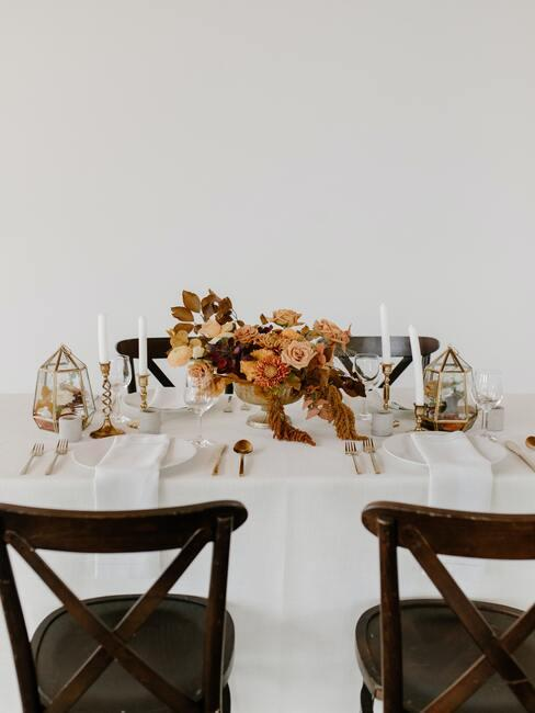 zwarte stoelen aan een gedekte tafel met een wit tafelkleed