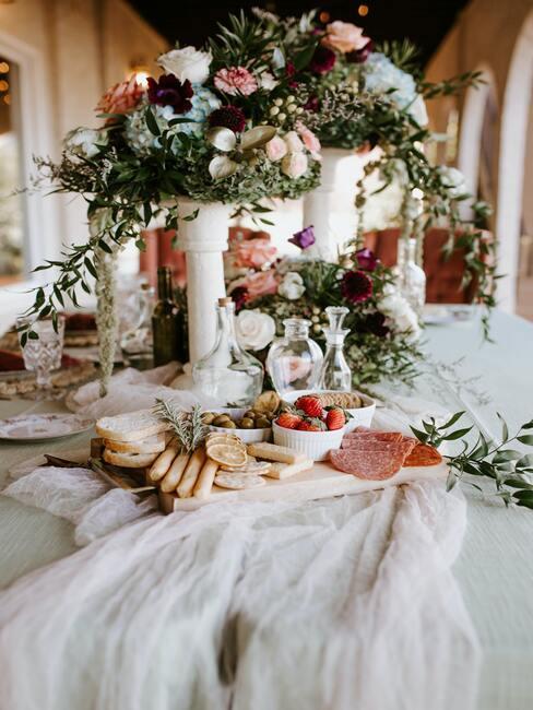 witte tafel met hoge witte vazen met bloemen