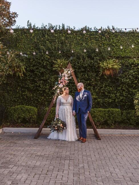 bruidspaar in een tuin met groene planten