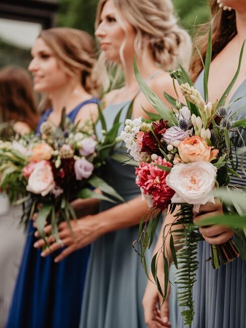 bruidsmeisjes in blauwe jurken met roze bloemen
