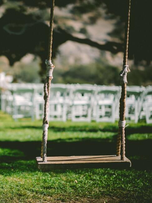 witte stoelen met een houten schommel