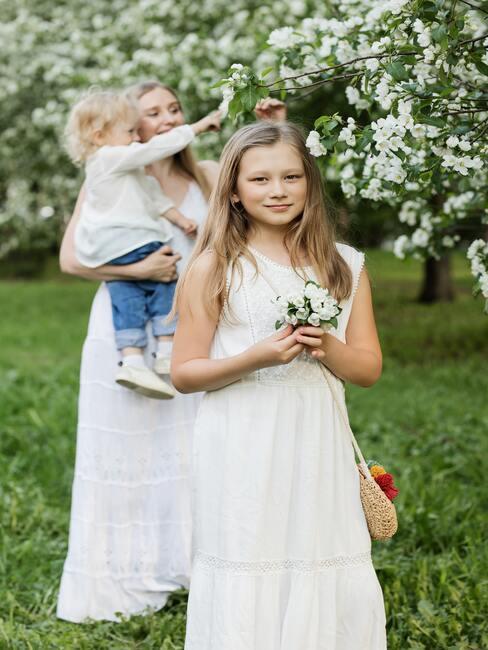 meisje in een witte jurk met bloemen vast
