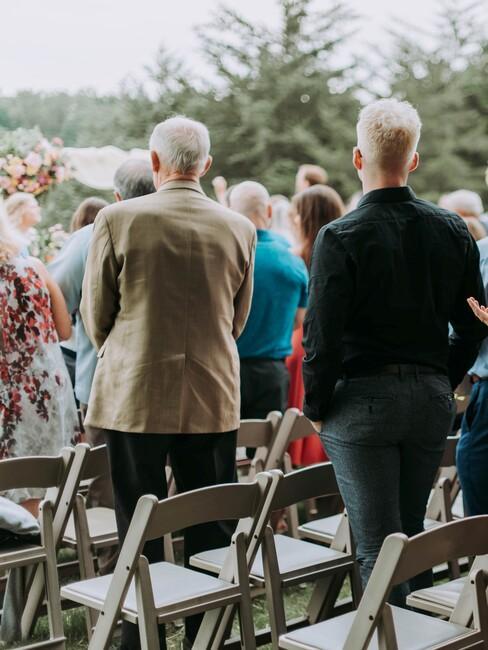 witte stoelen langs het altaar met staande mensen tijdens de huwelijksceremonie