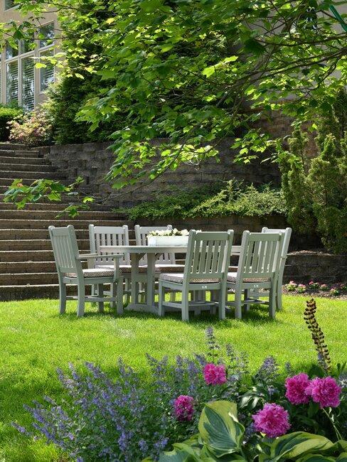 tuin met gras en een witte eettafel met stoelen