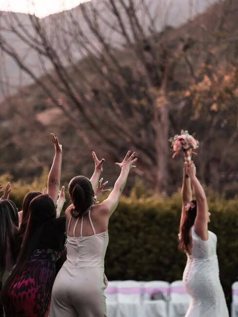 bruid die roze boeket gooit