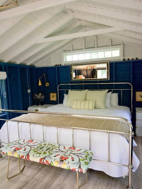 blauwe muur met een gouden bed en gele kussens