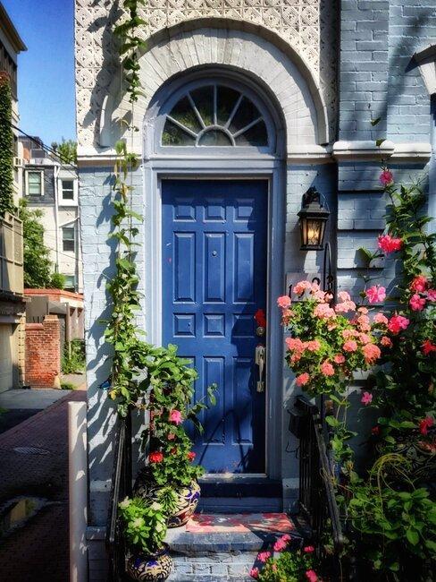 blauwe voordeur met lantaarntje en bloempotten