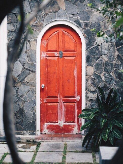 oranje voordeur met stenen muur