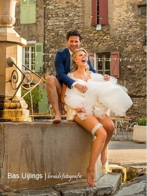 Blij bruidskoppel op een fontein in de zon