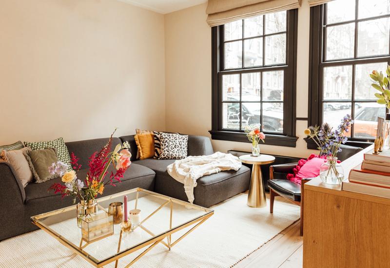 woonkamer met een grijze bank gekleurde kussens en gouden bijzettafel