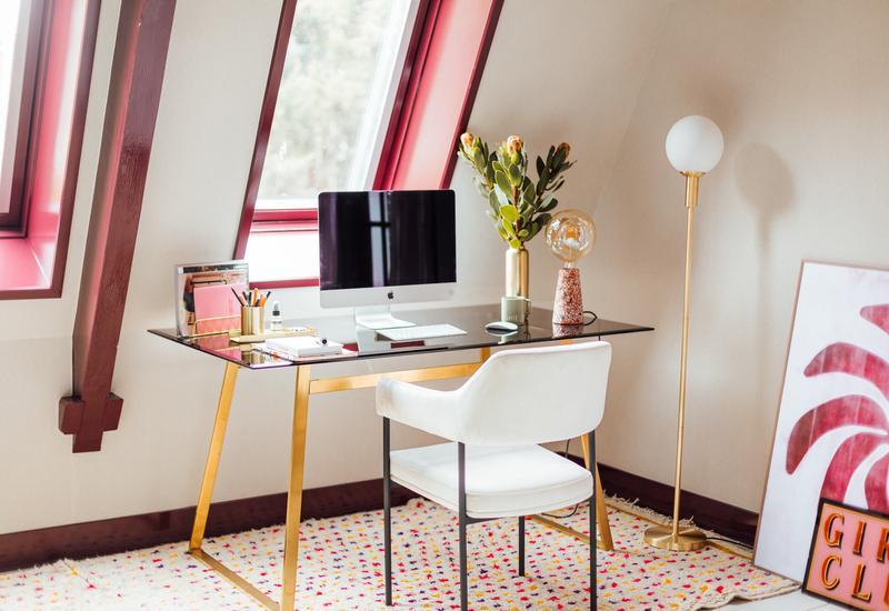 gouden bureau met witte stoel en roze kozijnen