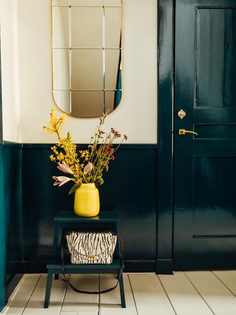 donkergroene deur en tafeltje met gele vaas