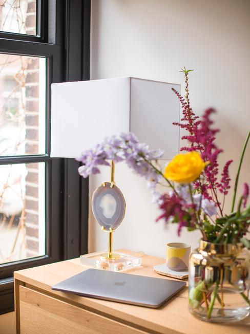 houten kast met witte lamp en bloemen in een glazen vaas