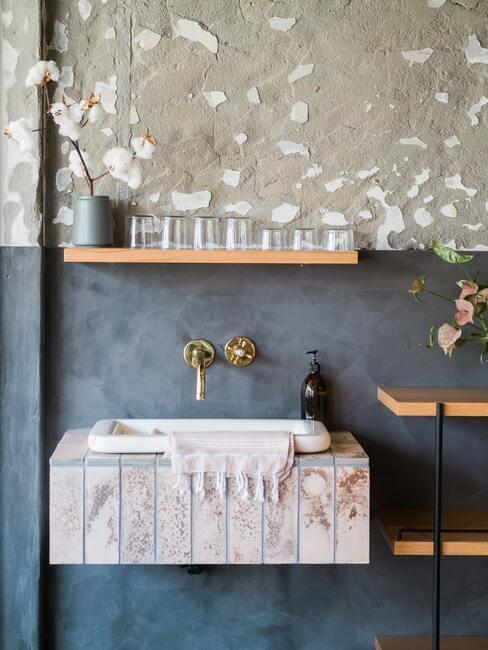 blauwe muur met witte spoelbak en houten wandmeubel