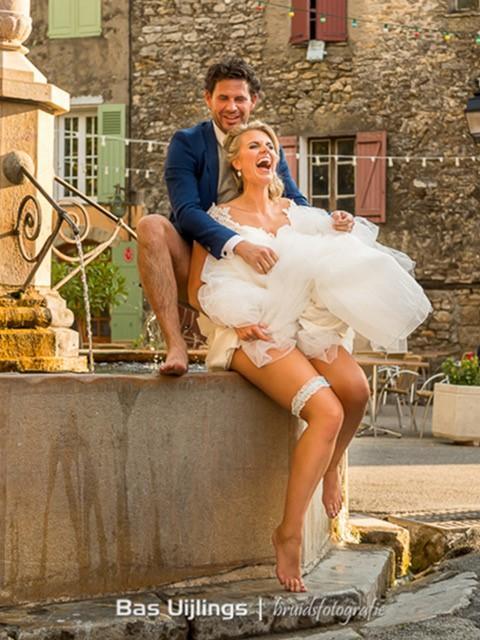 Gelukkig bruidspaar zit op fontein in de zon