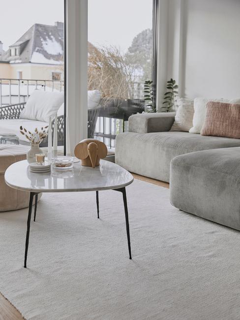 grijze bank met zwarte tafel en witte schuifdeur