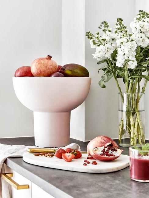 fruitschaal en bloemen in een vaas