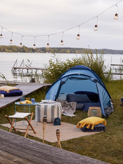 blauwe tent met zwarte lampjes en gele kussens