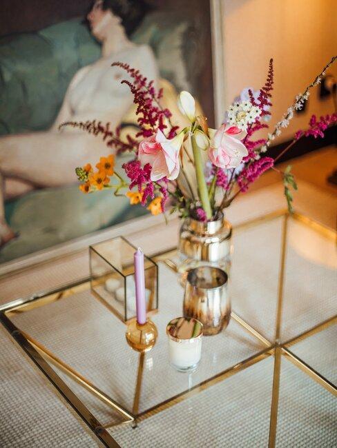 glazen tafel met gouden accenten en vaas met roze bloemen