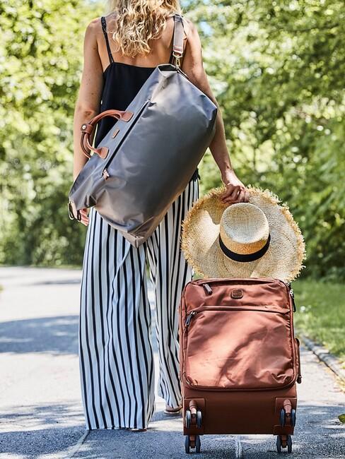 bruine koffer die een vrouw rolt met een rieten hoed