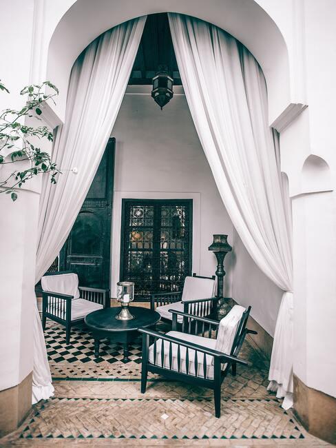 zwarte stoelen met witte kussens en witte gordijnen
