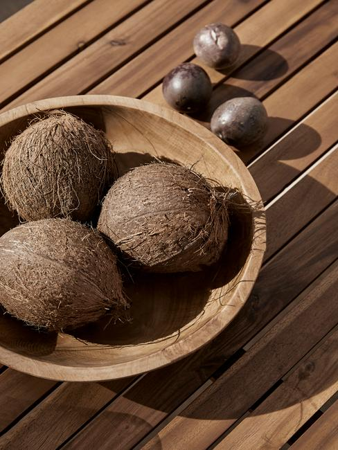 houten tafel met een houten schaal met kokosnoten