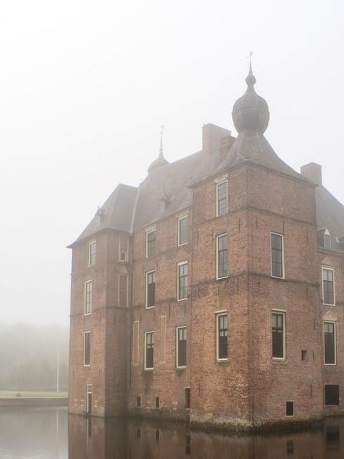 kasteel met slotgrachten en mist