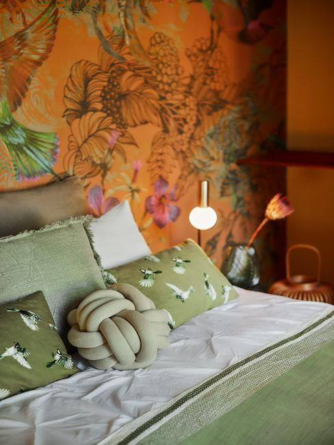 oranje muur met print en een bed met groene kussens en dekens