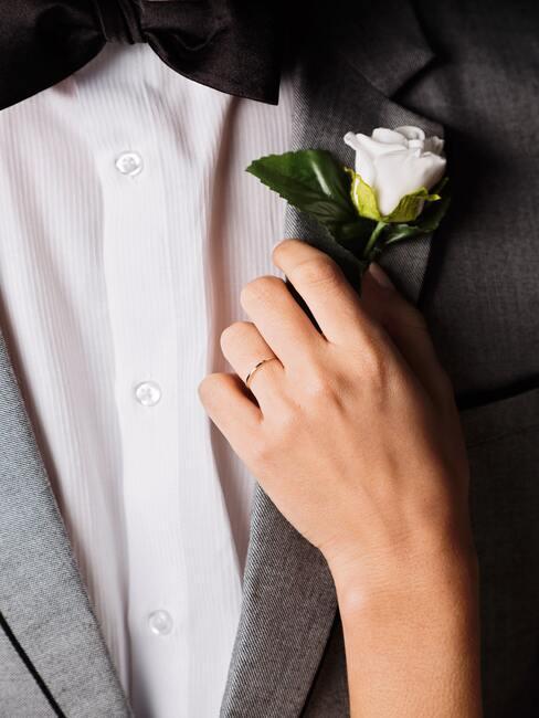 man in pak met een witte roos