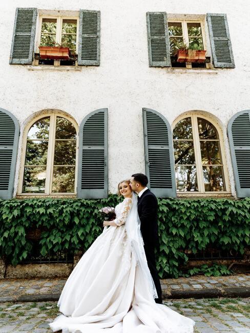 bruidspaar voor wit landhuis