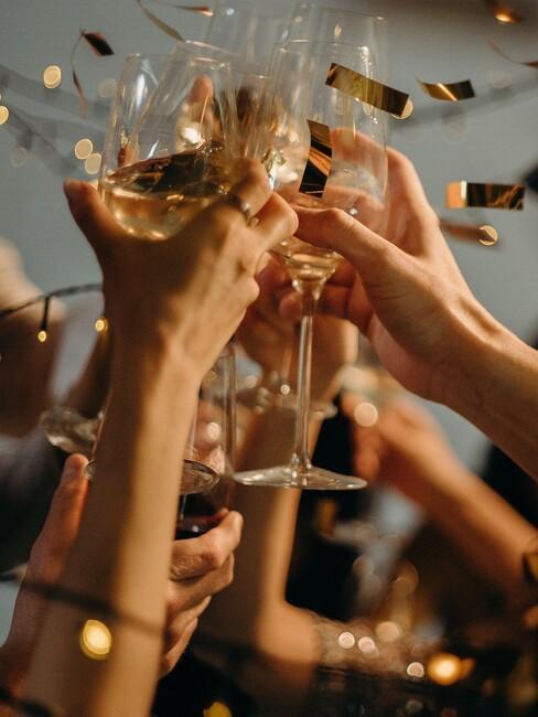 wijnglazen in de lucht met gouden confetti
