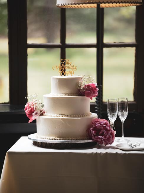 witte taart met roze bloemen en champagne glazen