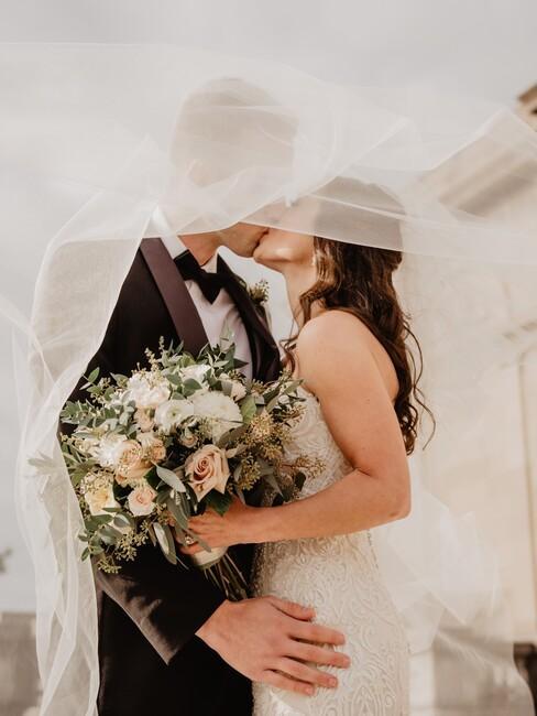 bruid en bruidegom aan het kussen onder de sluier