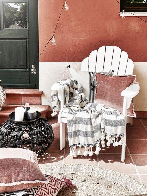 witte stoel met een rood kussen en een rode muur