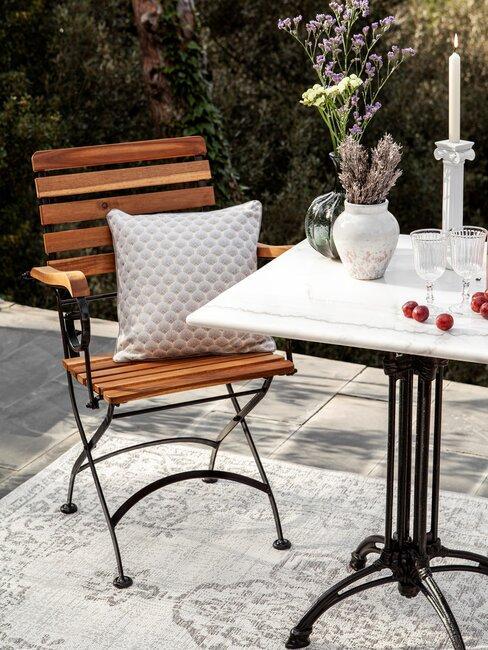 houten stoel met een beige kussen en marmere tafel