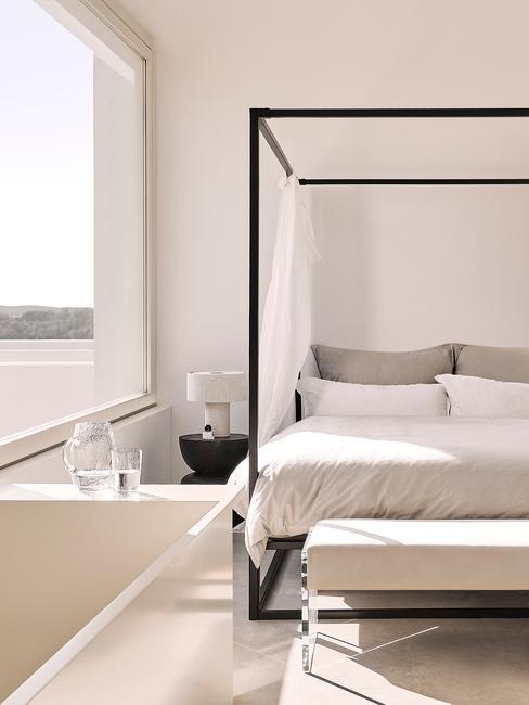 slaapkamer met zwart hemelbed met beige dekbed