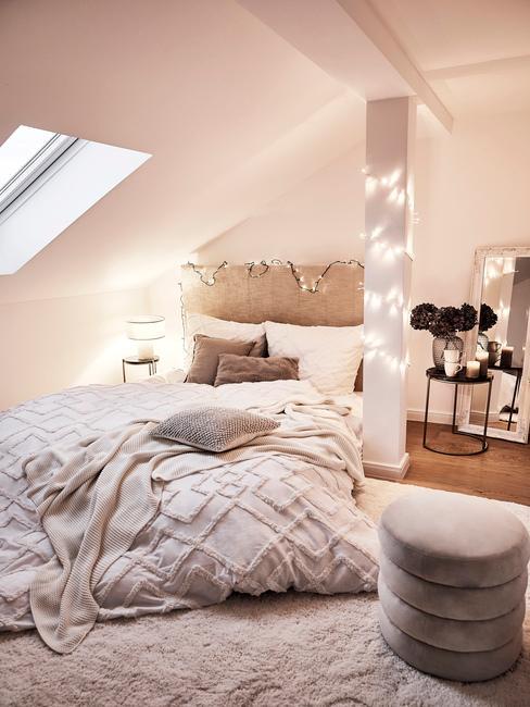 slaapkamer met beige boxspring met lampjes en grijze poef