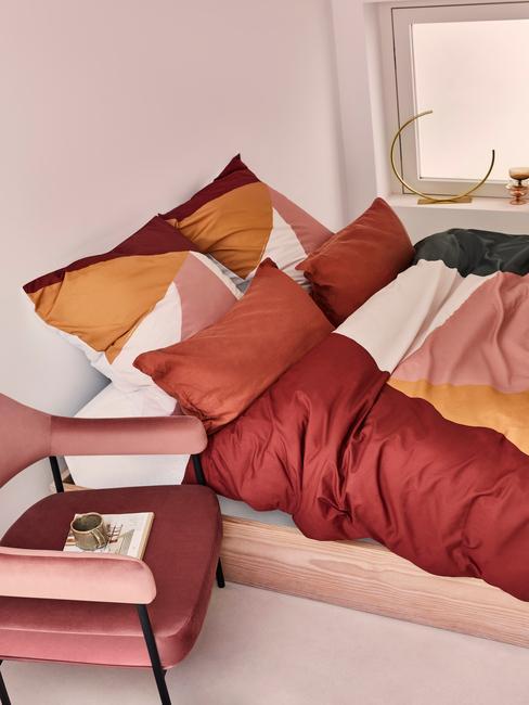 houten bed met rood en oranje dekbed en rode velvet stoel