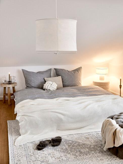 grijs dekbed met witte sprei en beige hanglamp