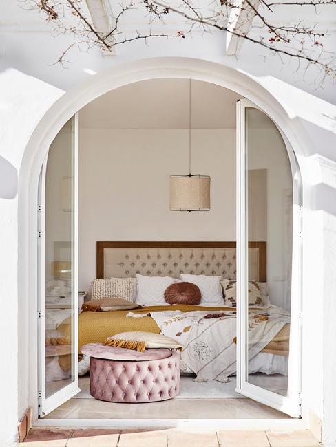 slaapkamer met witte openslaande deuren met een okergeel dekbed