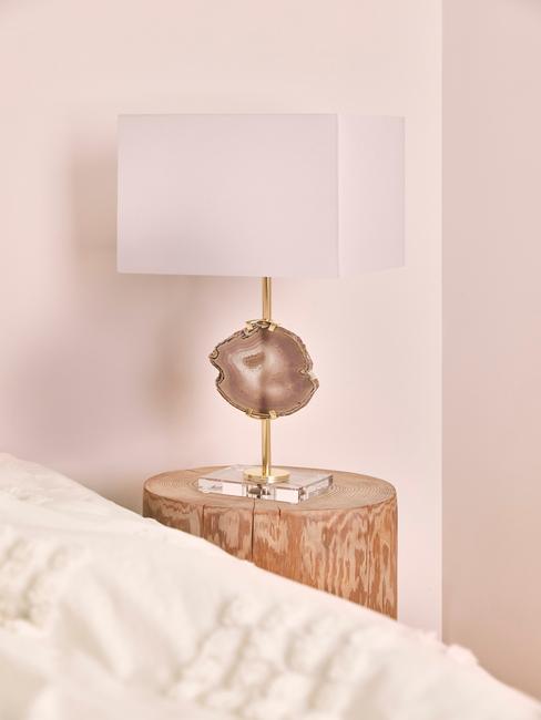 witte lamp met gouden voet op een houten bijzettafel