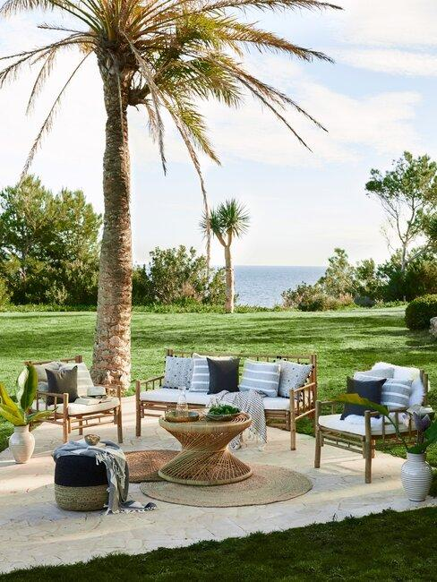 tuin met gras en loungeset en palmbomen