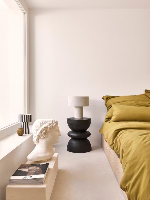 slaapkamer met zwart nachtkastje met beige lamp