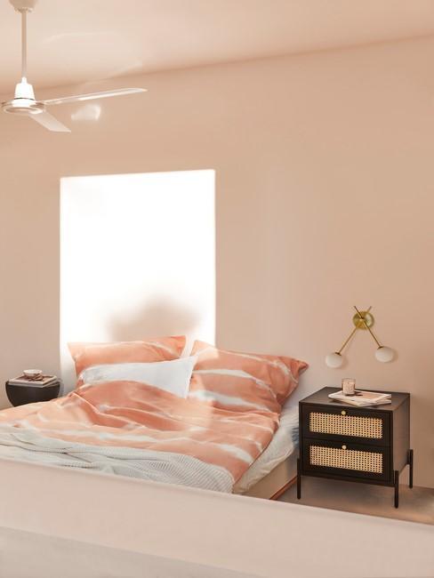 lichtroze slaapkamer met zwart nachtkastje en gouden wandlamp