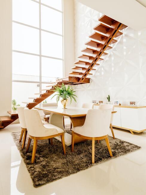 houten zwevende trap met witte stoelen en houten tafel