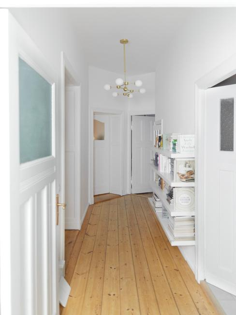 witte gang met houten vloer en witte kast met gouden hanglamp