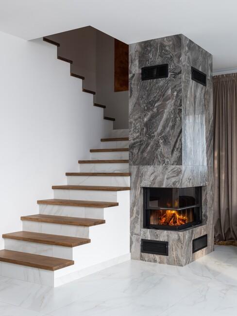 houten trap met witte onderkant en openhaard