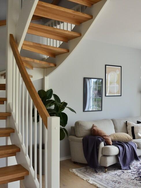 houten trap met witte leuning en grijze bank
