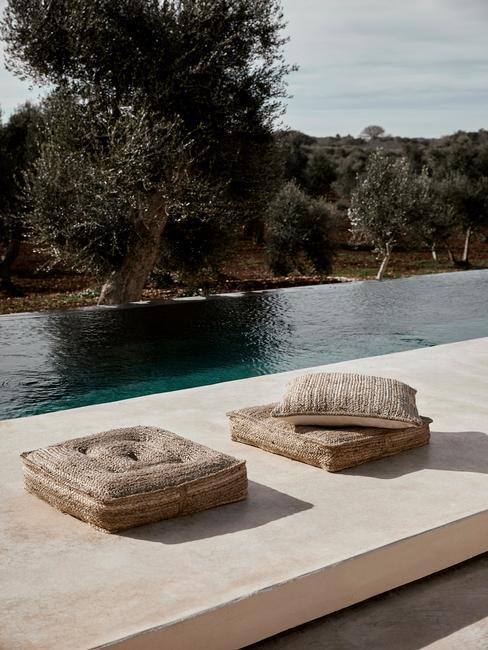 rieten zitkussens naast een zwembad